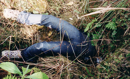 <p>A massacre victim shoved in a hole in Colombia. Photo by Garry Leech</p>