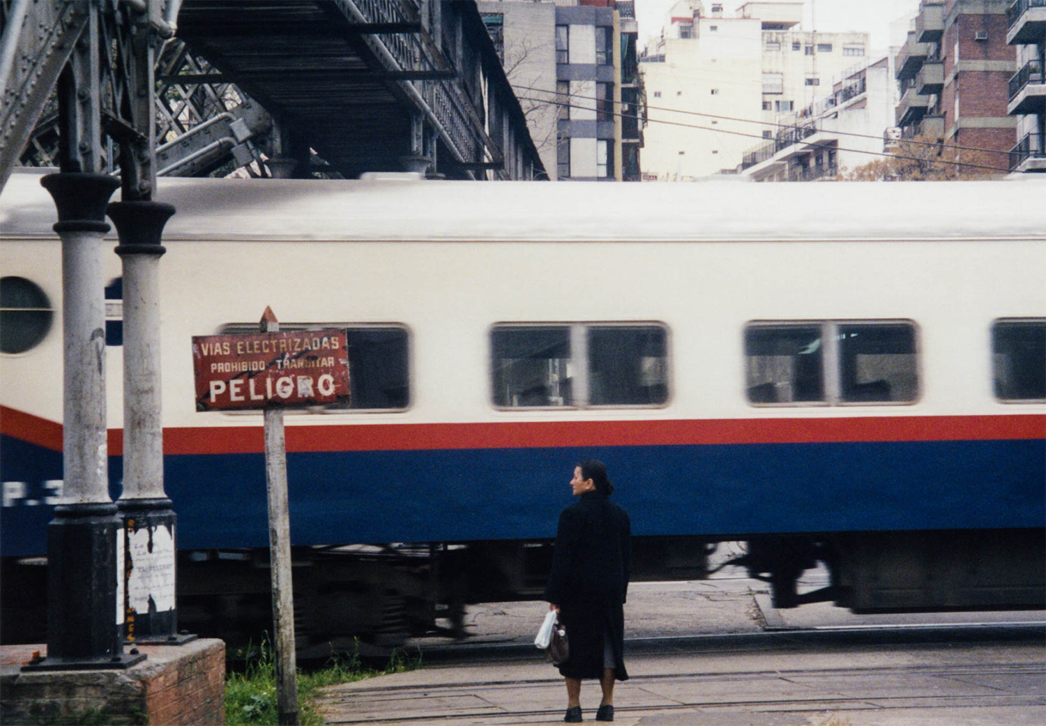 <p>A woman waits at a level crossing in Buenos Aires.</p>