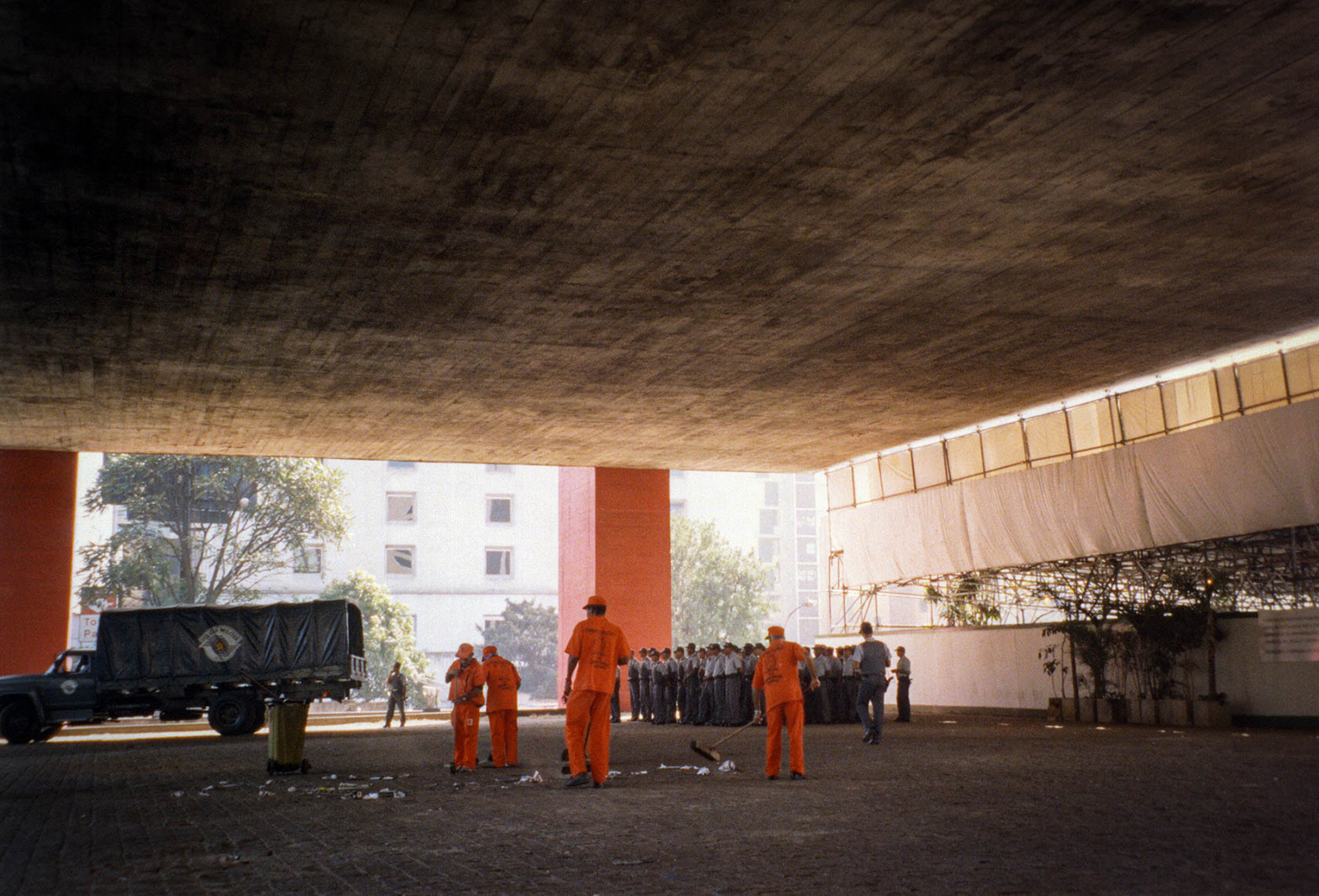 <p>Security forces muster while a team of workers sweep the space beneath the hulking mass of the Museu de Arte de São Paulo.</p>
