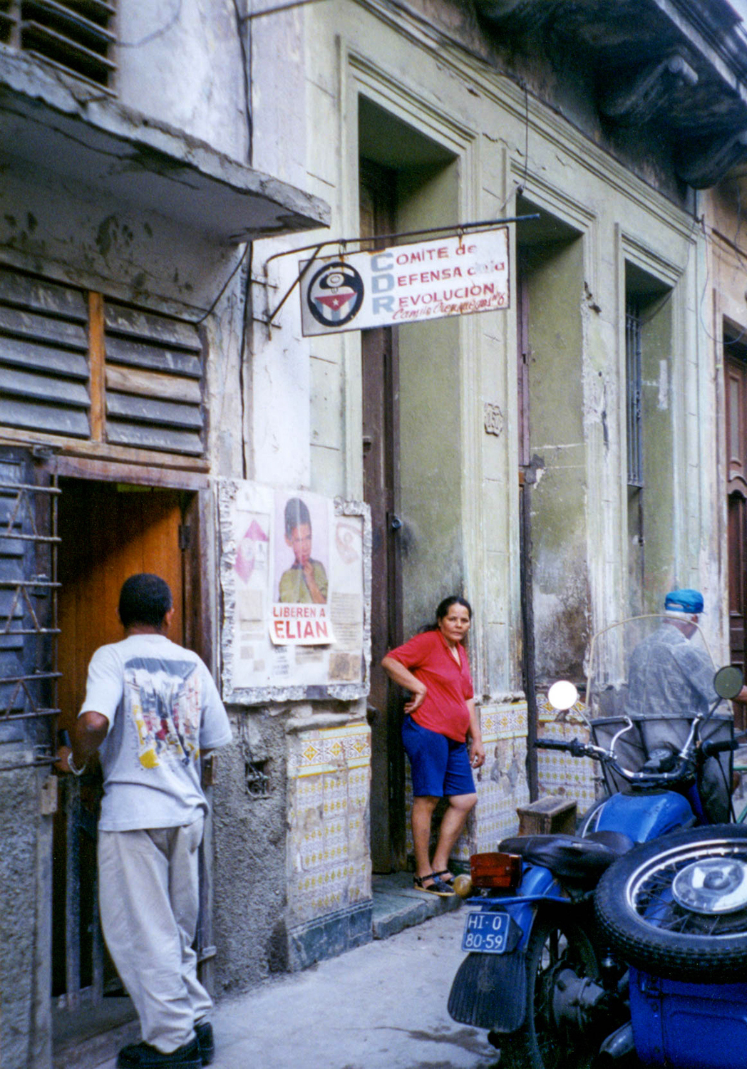 <p>A woman stands near an office for the Committee for the Defence of the Revolution. Set up in the early days of the Cuban revolution to counter saboteurs and counter-revolutionary activities, they have persisted as a sort of hybrid 'neighbourhood watch' and community welfare association. Critics contend they constitute little more than a vast network of informants for the government, while defenders claim they are essential for the local coordination of everything from vaccination campaigns and blood drives to hurricane evacuations.</p>