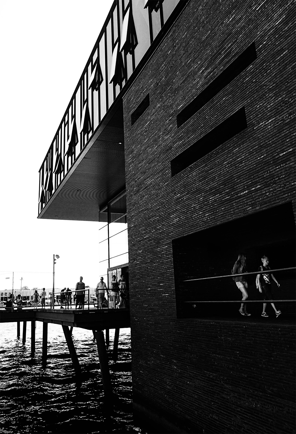 <p>Saturday strollers along the waterfront pass through light and shadows.</p>