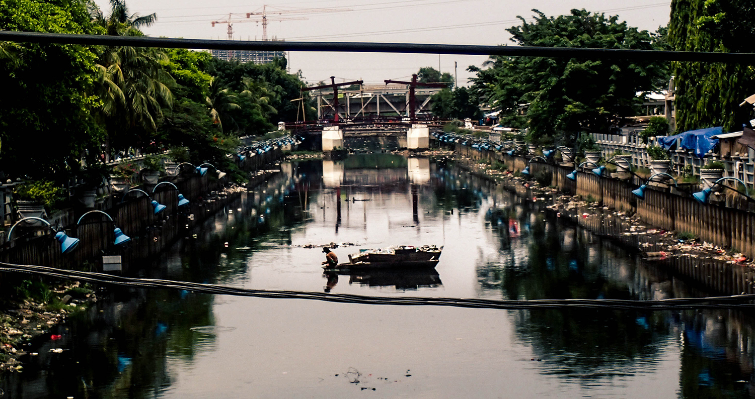 <p>A man in his boat in a Jakarta canal.</p>