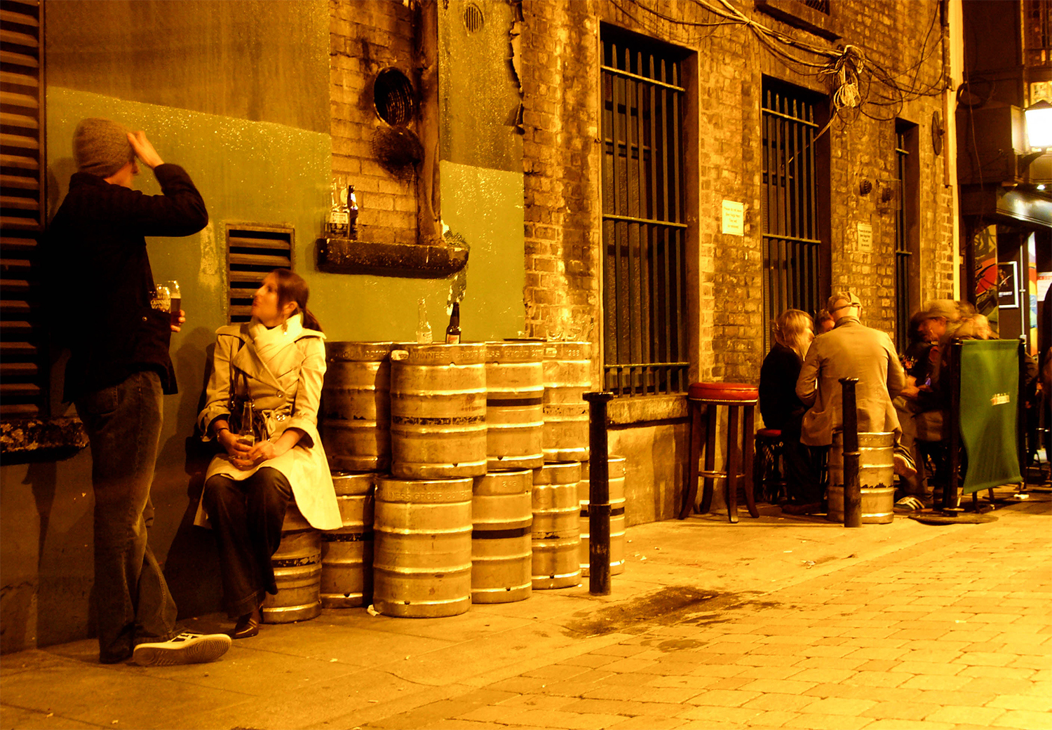 <p>Empty kegs provide impromptu seating as the night wears on in Dublin's Dame Lane.</p>