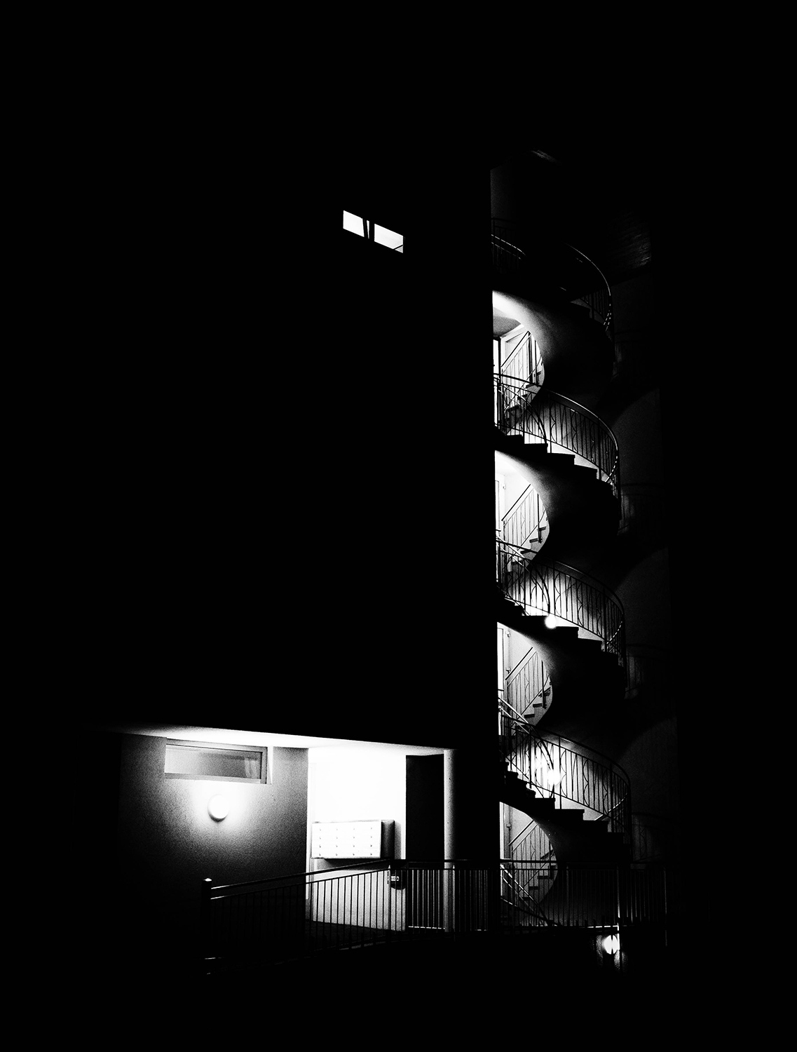 <p>The spiral staircase of a modern flat takes on a different air by night.</p>