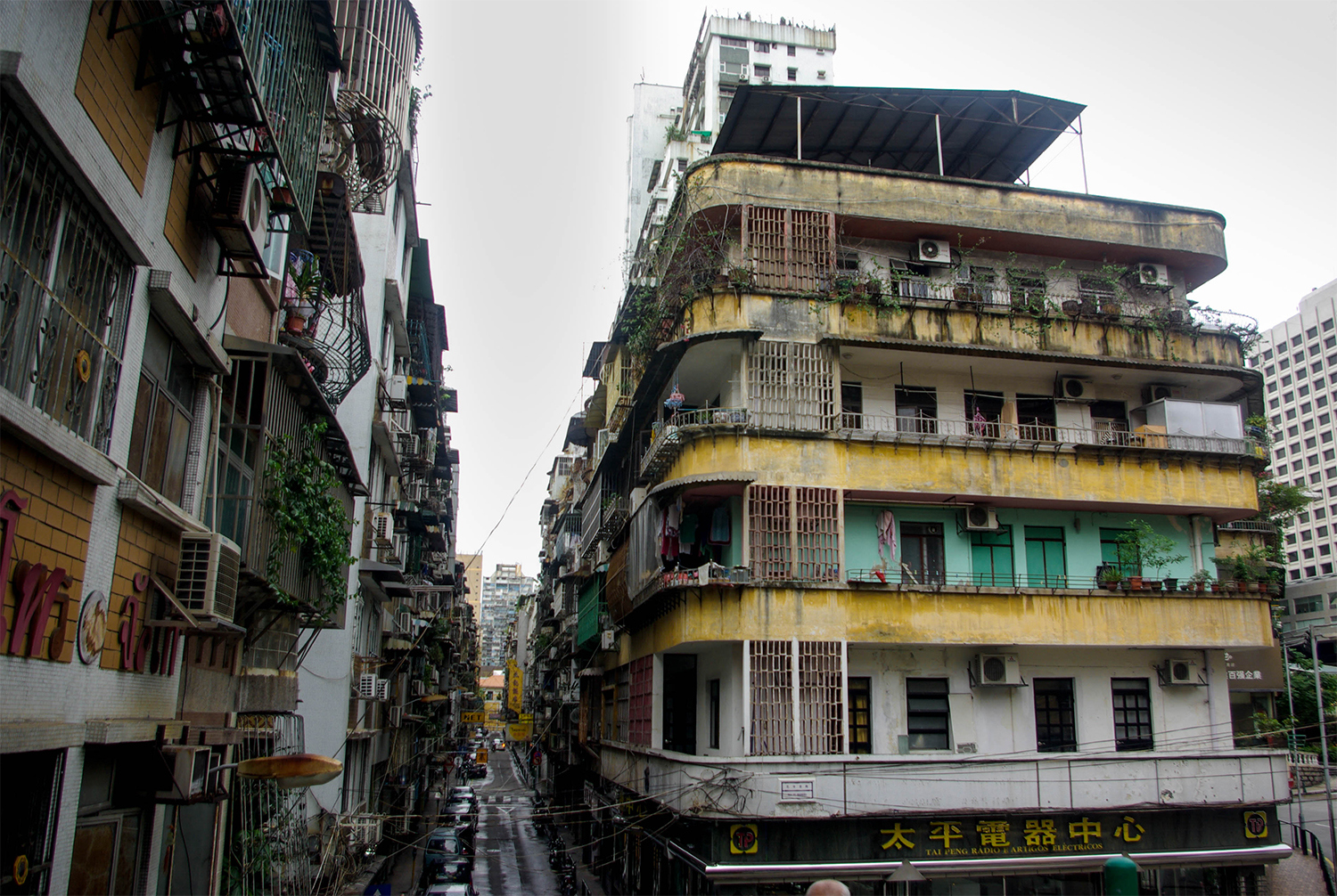 <p>Brightly painted bands run along the balconies of a building on Rua do Brandão. A typically tight Macanese street squeezes in alongside. </p>