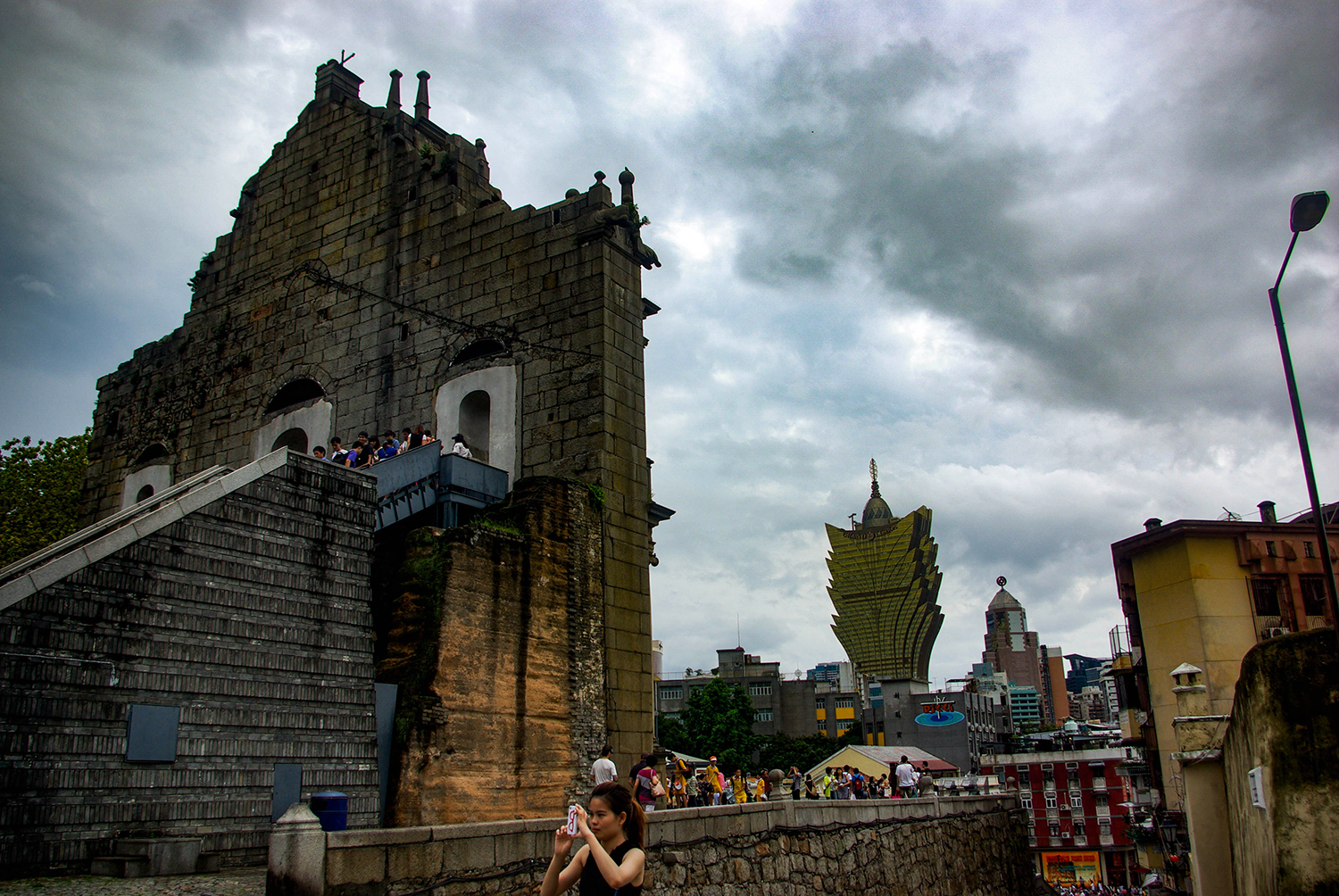 <p>A woman turns her back on the visitors clogging the steps of Macao's landmark Igreja de São Paulo ruins and the skyline of casino towers to capture her own take on the densely populated city.</p>