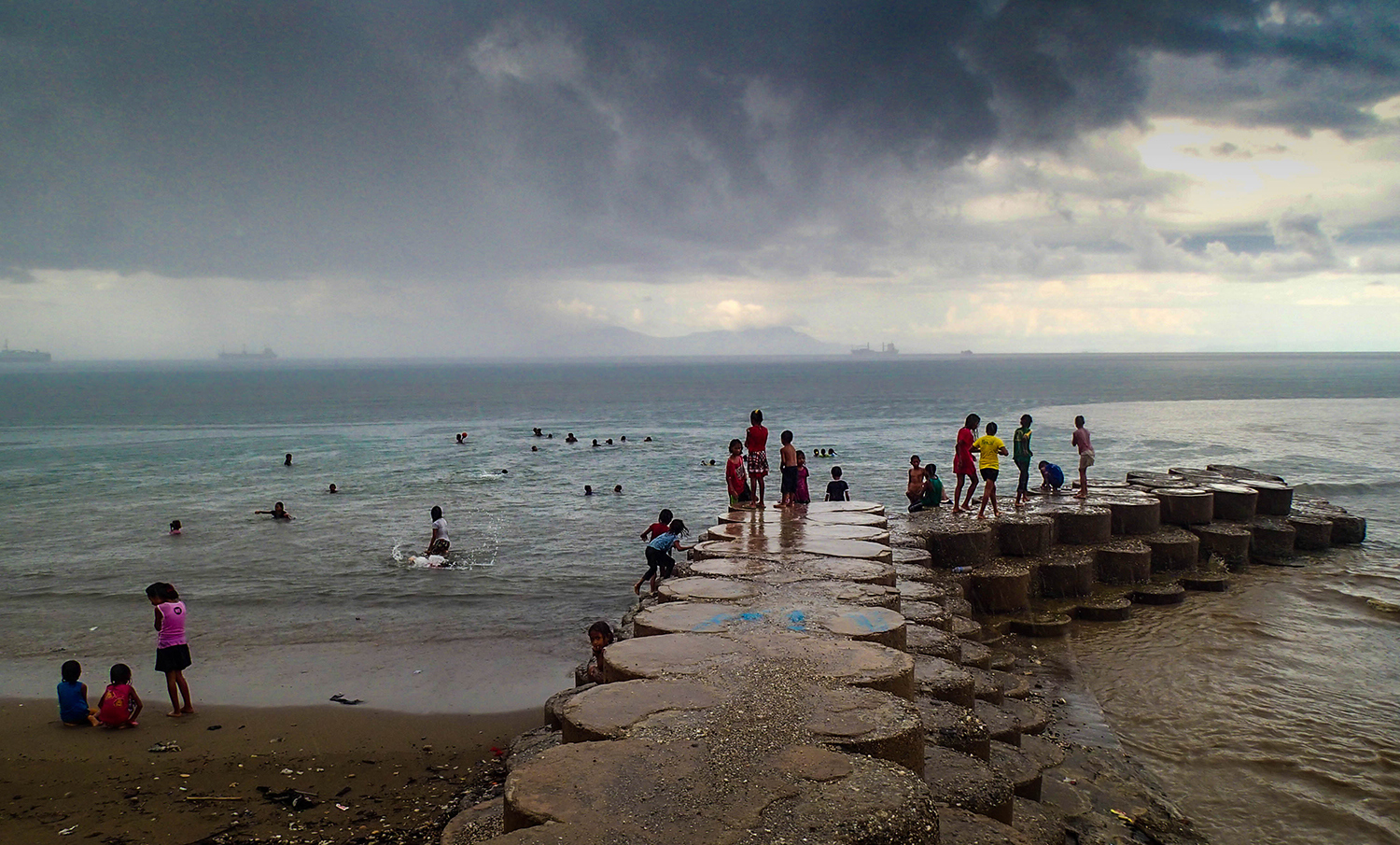 <p>Children playing along Dili's waterfront after the daily rainstorm.</p>