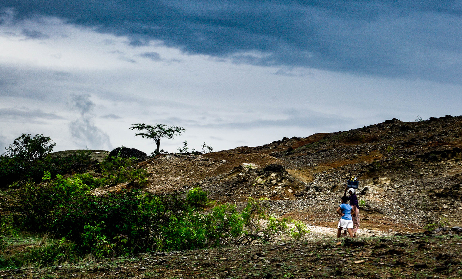 <p>Two people walking along a path somewhere near Laga, in eastern Timor-Leste.</p>