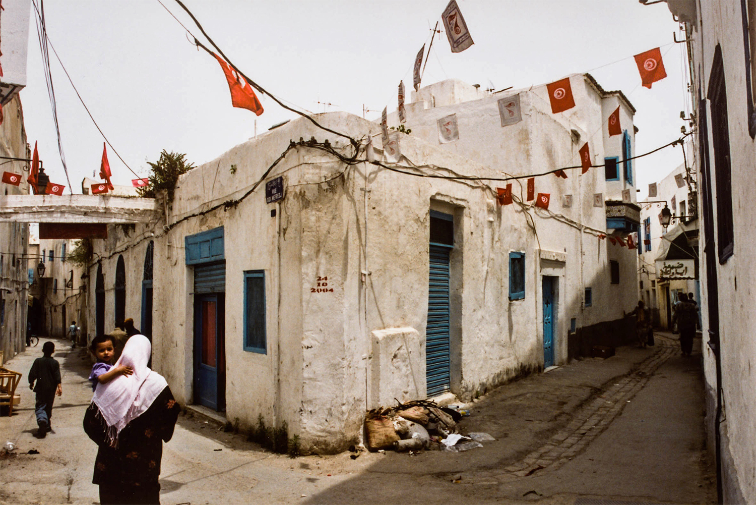 <p>A woman and her children on a backstreet of Tunis's Medina. <br /></p> <p>The date on the wall refers to the Tunisian general election from the previous year, which (unsurprisingly) saw the highly corrupt president Zine El Abidine Ben Ali 're-elected' for a fourth time – with a mere 94.9 percent of the vote. A few years later, Ben Ali's flagrant misrule sparked the Arab Spring that permanently removed him from power.</p>